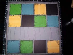 All of the paper squares laid out on the gray background paper prior to adding the embellishments. photo by Meredith at TheFunTimesGuide.com