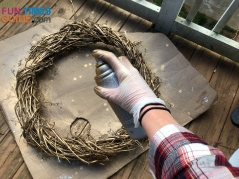 Painting this large grapevine wreath with gold spray paint.